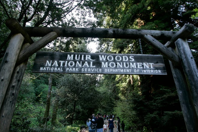 Visitors walk along a pathway near the entrance to the Muir Woods National Monument, named after John Muir, in Marin County, Calif. The Sierra Club is reckoning with the racist views of founder John Muir, the naturalist who helped spawn environmentalism. The San Francisco-based environmental group said Wednesday, July 22, 2020, that Muir was part of the group's history perpetuating white supremacy.