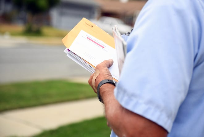 A mail carrier for the Salinas post office holds a stack of mail.  The U.S. Postal Service is expected to lose $22 billion in the next 12 months. July 21, 2020.