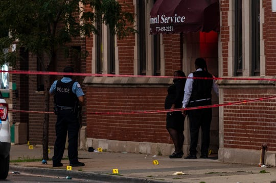 Chicago police investigate the scene of a mass shooting where more then a dozen people were shot in the Gresham neighborhood, of Chicago, Tuesday, July 21, 2020.  (Tyler LaRiviere/Chicago Sun-Times via AP) ORG XMIT: ILCHS808