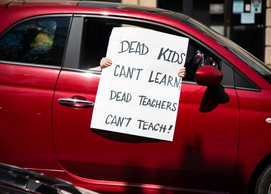 "A protestor holds a sign out a car's window during the ""Dead Kids Can't Learn; Dead Teachers Don't Teach"" honkathon in front of the Andrew Johnson Building in Downtown Knoxville, Tenn., on Friday, July 17, 2020. The honkathon was in protest of Knox County schools' reopening plan amid the coronavirus pandemic."