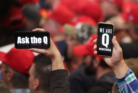 Supporters of President Donald Trump hold up phones displaying messages referring to the QAnon conspiracy theory at a campaign rally at Las Vegas Convention Center on Feb. 21, 2020.