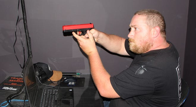 Trent Whited, Shooter's Corner range manager, sets the range on a laser pistol in the simulation room where shooting training starts. Firearms and ammunition sales as well as the number of people wanting to learn how to shot have climbed rapidly since the coronavirus pandemic.