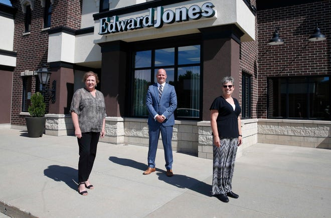 Edward Jones financial advisor Mark Ellison stands with Lisa Peterson, left, and Kristi Meyer outside the Ankeny location.
