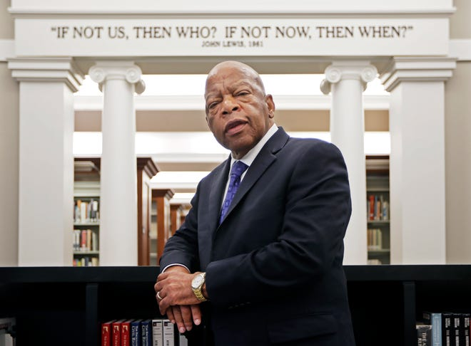 In this Nov. 18, 2016, file photo, U.S. Rep. John Lewis, D-Ga., poses for a photograph under a quote of his that is displayed in the Civil Rights Room in the Nashville Public Library in Nashville, Tenn. Lewis died July 17, 2020  of pancreatic cancer.