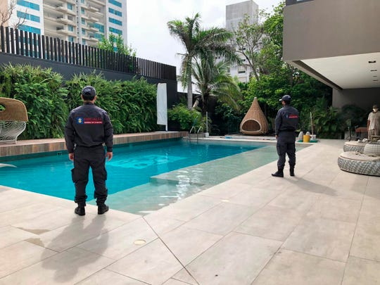 In this photo distributed by Colombia's Attorney Generals Office, officials pose with their backs to the camera by a pool on a property allegedly belonging to Alex Saab in Barranquilla, Colombia, Wednesday, July 22, 2020.