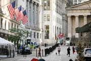 People walk by the New York Stock Exchange, left, Tuesday, July 21, 2020.