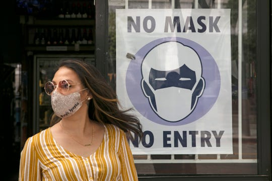 A woman walks out of a liquor store past a sign requesting its customers to wear a mask Tuesday in Santa Monica, Calif.