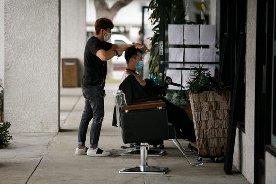 Hairstylist Travis Vu gives a haircut to Minh Dao at his outdoor hair salon in Fountain Valley, Calif., on Wednesday. The worsening COVID pandemic risks choking off the U.S. economy's fragile recovery and turn what some investors hoped would be a sprint back to normal into a long hard slog.