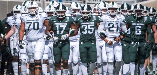 """The Michigan State football program announced it has placed workouts on """"pause"""" because one of its staff members tested positive for COVID-19, the athletic department announced Wednesday night."""