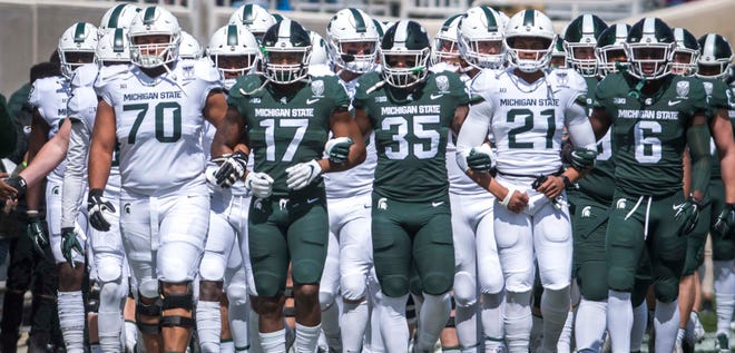 "The Michigan State football program announced it has placed workouts on ""pause"" because one of its staff members tested positive for COVID-19, the athletic department announced Wednesday night."