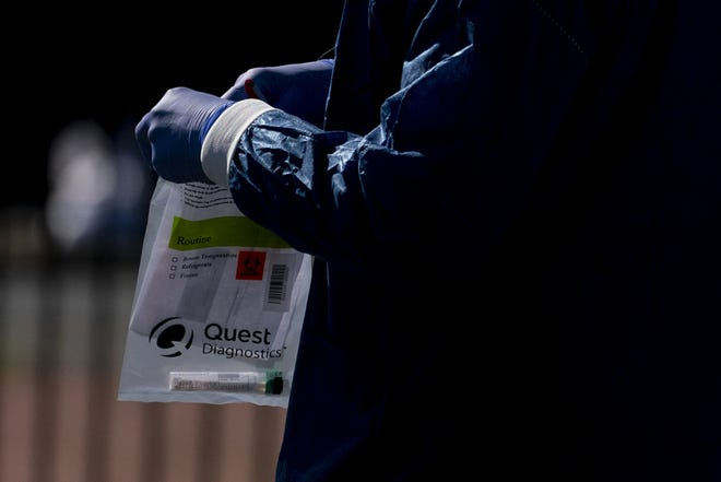 A Children's National Hospital healthcare worker holds a Quest Diagnostics bag containing a COVID-19 swab at a coronavirus drive-thru testing site on April 2 at Trinity Washington University in Washington, D.C. in April of 2020.