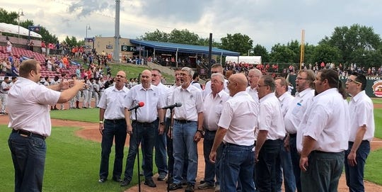 The Old Capitol Chorus sings the national anthem before a game.