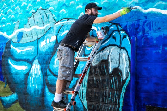 Artist Jonathan Sims works on a mural depicting a prehistoric underwater scene in the alleyway between Dubuque and Linn Streets, Thursday, July 23, 2020, at Elray's Live & Dive in Iowa City, Iowa.