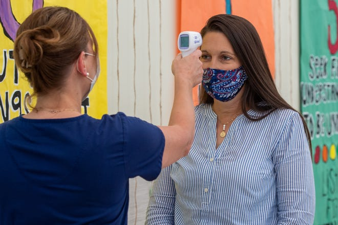 Julie Buller, Supervisor of Nurses for Health Services, conducts training with LJ Alleman Assistant Principal Allison Champagne, on using thermometers to take temperature at schools. The Lafayette school system is preparing to return to school on Aug. 17.