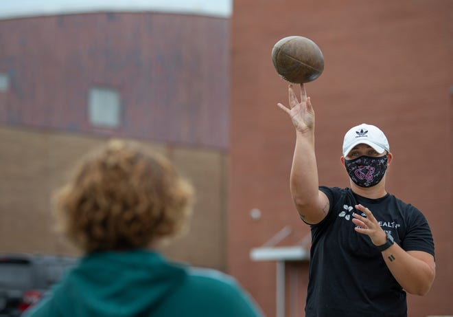 High school athletic trainers are required to follow strict Covid-19 guidelines as teams ramp up for the fall football season. Bullitt Central trainer Sam Klein tosses a football with a team member who is rehabbing an injury. July 23, 2020