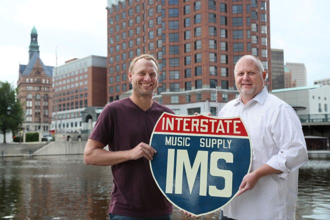 Mark Becker co-founder and COO of Geneva Supply, left, and Jeff Peterson co-founder and CEO, have purchased Cascio Interstate Music. The long-time New Berlin-based business will now operate as an e-commerce firm serving the Milwaukee area and beyond. Here, they're holding the original Interstate Music sign. Michael Sears/Milwaukee Journal Sentinel