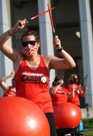 Wendy Piasentin leads The Livonia Beat Cardio Drumming group in front of St. Mary Mercy Hospital on July 22.