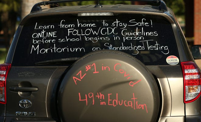 """Teachers take part in a """"motor march"""" at Encanto Park in Phoenix on July 22, 2020, to protest reopening K-12 schools for in-person classes."""