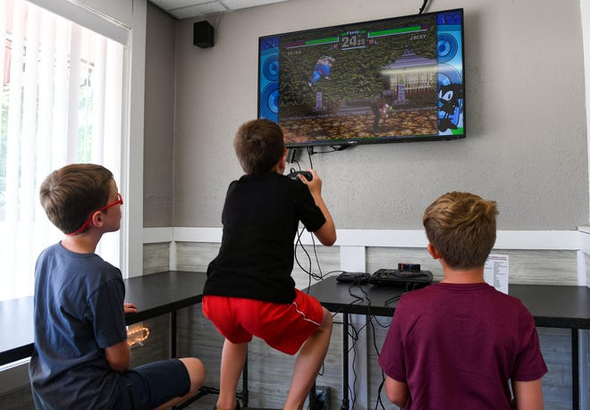 Kids playing video games on a Sega Genesis console.