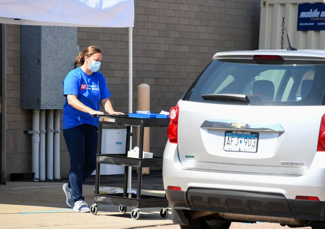 A Walgreens employee approaches a car with coronavirus testing supplies on Thursday, July 23, at the 41st Street location in Sioux Falls.