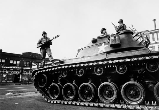 Federal soldiers stand guard on a tank in a Detroit street on July 25, 1967 during riots that erupted in Detroit following a police operation.