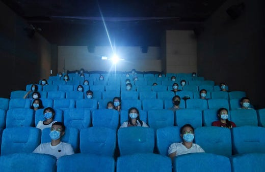 Movie-goers wearing masks to protect themselves from the coronavirus are spaced apart as they watch a movie in a newly reopened cinema in Hangzhou in eastern China's Zhejiang province on Monday, July 20, 2020. China is going back to the movies. Following months of closure, limited numbers of movie goers were allowed back Monday in cities where the risk of virus infection is considered low.