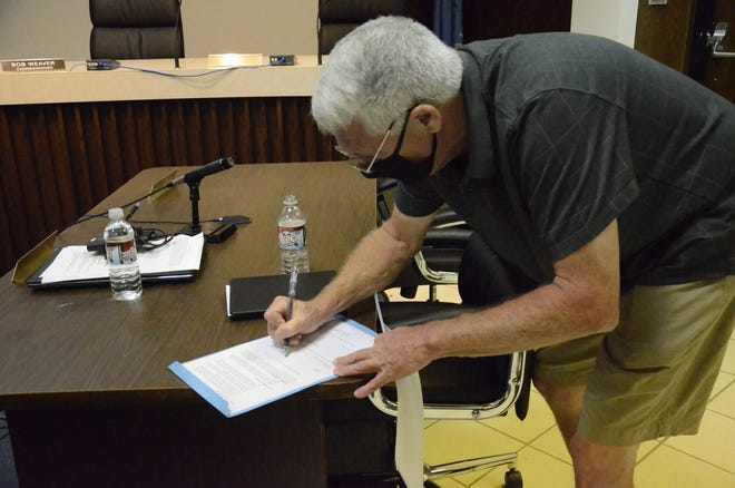 Due to rising numbers in COVID-19 cases, Mayor Ed Bolt signs an ordinance requiring face coverings to be worn in places open to the public.