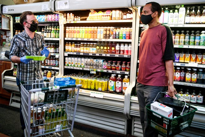 Christopher Jones, left, and Jerome Smith chat at the French Broad Food Co-Op in Asheville July 24, 2020.