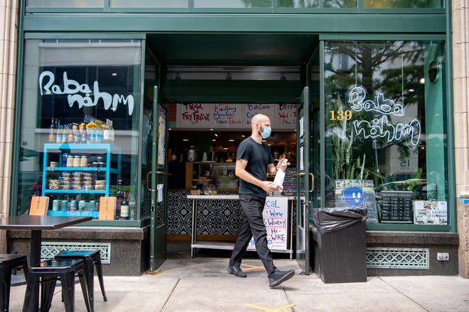 Alex Marjanovic walks to the patio of Baba Nahm in downtown Asheville to wipe down and disinfect tables on July 24, 2020. Ordering at the grab and go Middle Eastern food restaurant has been moved to the doorway with no customers allowed inside the restaurant but limited patio seating is still available.