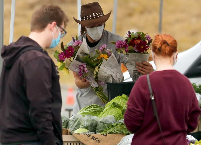 James Richert arranges a display of fresh flower bouquets for sale in the Skokomish Valley Farms booth at the Bremerton Farmers Market at Pendergast Park on Thursday, July 23, 2020.