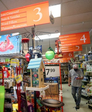 FILE — With a bottle glass cleaner in hand, customer Bill McKenna makes his way down the aisle and heads for the checkout at Coast Do It Best Hardware in Poulsbo in July 2020.