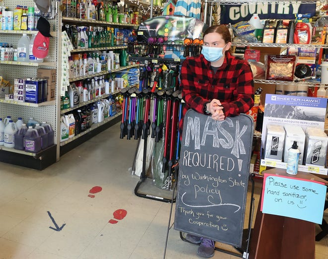 Hannah Ronning leans against one of the Mask Required signs as she greets customers coming through the front door at Coast Do It Best Hardware in Poulsbo on Friday, July 24, 2020.