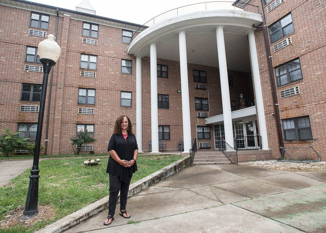 Soon to be retired director Kathleen Sims stand in front of Tiffin Tower, one of the first residences of the Chillicothe Metropolitan Housing Authority.