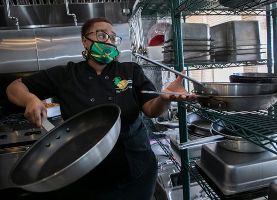 The Free Press is checking in with five women who have opened their restaurants in the middle of a pandemic. Flavors of Jamaica in Pontiac owner Reniel Billups, 39, reaches for cookware in the kitchen during a busy take out lunchtime Friday, July 24, 2020.