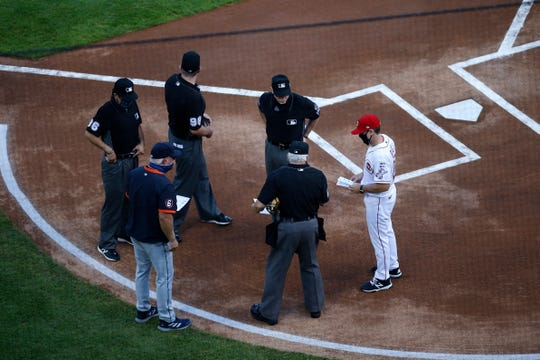 Detroit Tigers manager Ron Gardenhire reviews his lineup card with the umpiring crew before the first inning on Opening Day vs. the Cincinnati Reds at Great American Ball Park in Cincinnati on Friday, July 24, 2020.