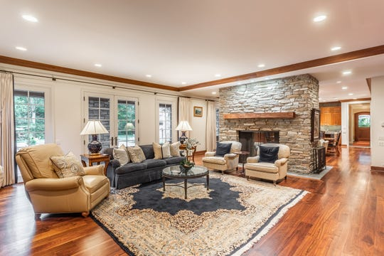 This Bloomfield Hills house has strong curb appeal and a resort-like backyard, very large, welcoming family room and kitchen, dressy formal areas, coach house apartment for staff or a studio. The family room is one-half of the 54-foot-long area that also contains the large kitchen, on the far side of the stone fireplace, which opens into both rooms. The hardwood floor and built-ins are all walnut, with sliding doors that can close to cover the televisions at each end of the room. At left, French doors open to a stone terrace.