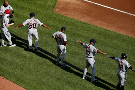 The Detroit Tigers gather at a distance before the first inning of the Major League Baseball Opening Day interleague game between the Cincinnati Reds and the Detroit Tigers at Great American Ball Park in downtown Cincinnati on Friday, July 24, 2020.