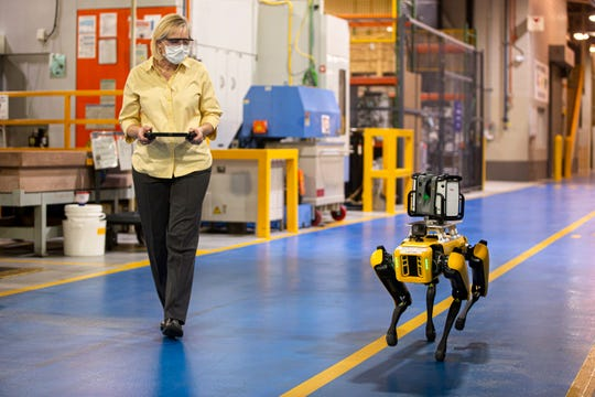 Paula Wiebelhaus navigates Fluffy the robot dog through the Van Dyke Transmission Plant. Ford is leasing two of the robots to map out its factories.