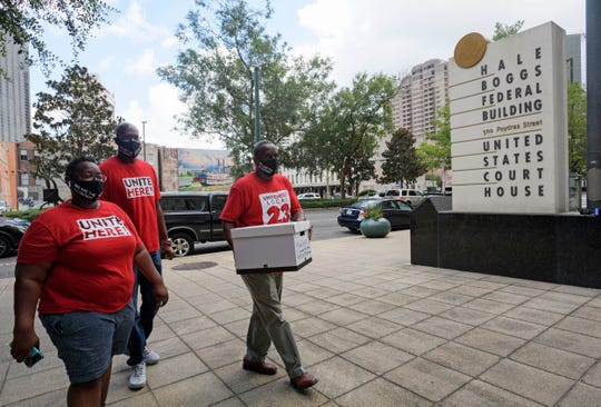 Leah Bailey, left, and members of UNITE HERE! deliver a box of signed petitions to Senator John Kennedy's office in New Orleans, La.