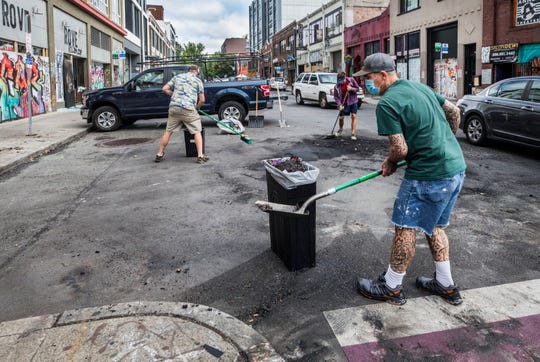Workers from a Capitol Hill property management company clean up the intersection of 11th and E. Pike Street, Thursday in Seattle, where clothing from the business, Rove, at left was looted and lit on fire in the street last night.