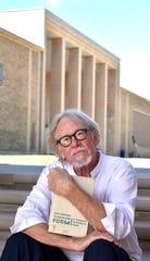 Eric Saarinen collaborated on a 2016 film about his father, modernist architect Eero Saarinen. Now he's tackling his grandfather, Cranbrook designer Eliel Saarinen. He holds one of Eliel's books.