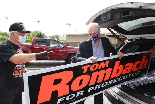 Maccomb County. prosecutor candidate Tom Rombach, right, delivers yard signs and posters to supporter Bob Slavko at the VFW post 6756 in Warren, Thursday, July 23, 2020.