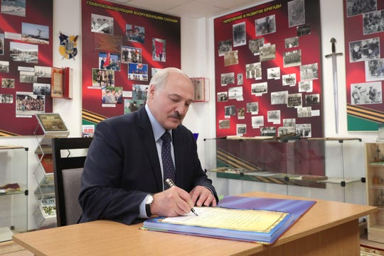 Belarusian President Alexander Lukashenko writes review as he his visits the military base in the town of Maryina Gorka in Belarus, Friday.