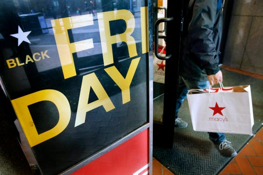FILE - In this Nov. 29, 2019 file photo, a shopper leaves Macy's in Boston on Black Friday. It's evident that the retail industry has felt the impacts of the COVID-19 pandemic. But what will that mean for Black Friday shopping? The annual November discount day usually features packed stores, long lines and massive discounts for holiday shoppers. But this year's Black Friday will be unlike anything we have  seen before.