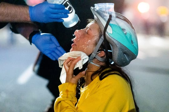 A medic treats Black Lives Matter protester Lacey Wambalaba after exposure to chemical irritants deployed by federal officers at the Mark O. Hatfield United States Courthouse on Friday in Portland, Ore.