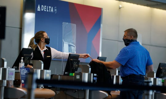 In this July 22, 2020 photo, a ticketing agent for Delta Airlines hands a boarding pass to a passenger as he checks in for a flight in the main terminal of Denver International Airport in Denver.