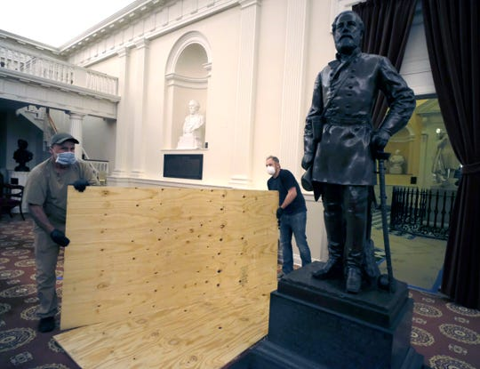 Workmen place plywood beside the statue of Robert E. Lee in the Old House Chamber inside the Virginia State Capitol in Richmond, VA Thursday night.