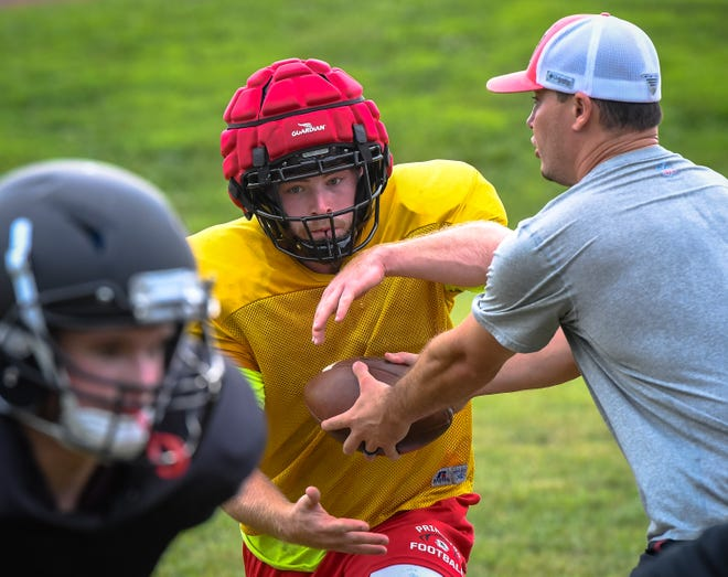 Ben Heidenreich takes a hand-off from head coach Jared Maners during an afternoon practice session for the Princeton Tigers Thursday, July 23, 2020.
