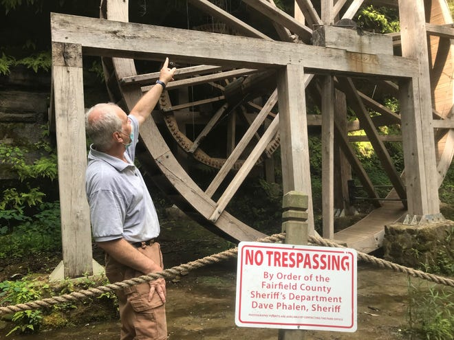 Rock Mill interpretive historian Jack Campbell points to damage trespassers have caused to the wheel at Rock Mill Park.
