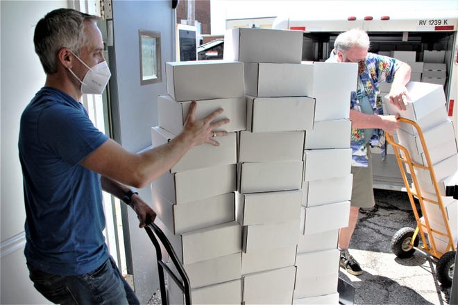 Matt Carbary, left, president of the Marion Area Chamber of Commerce, and Gus Comstock, right, executive director of Marion CANDO, unload a donation of PPE on Tuesday, July 21, 2020, at the chamber office. JobsOhio and One Columbus donated 600 PPE Safety Toolkits to the chamber for distribution to small businesses in Marion County.